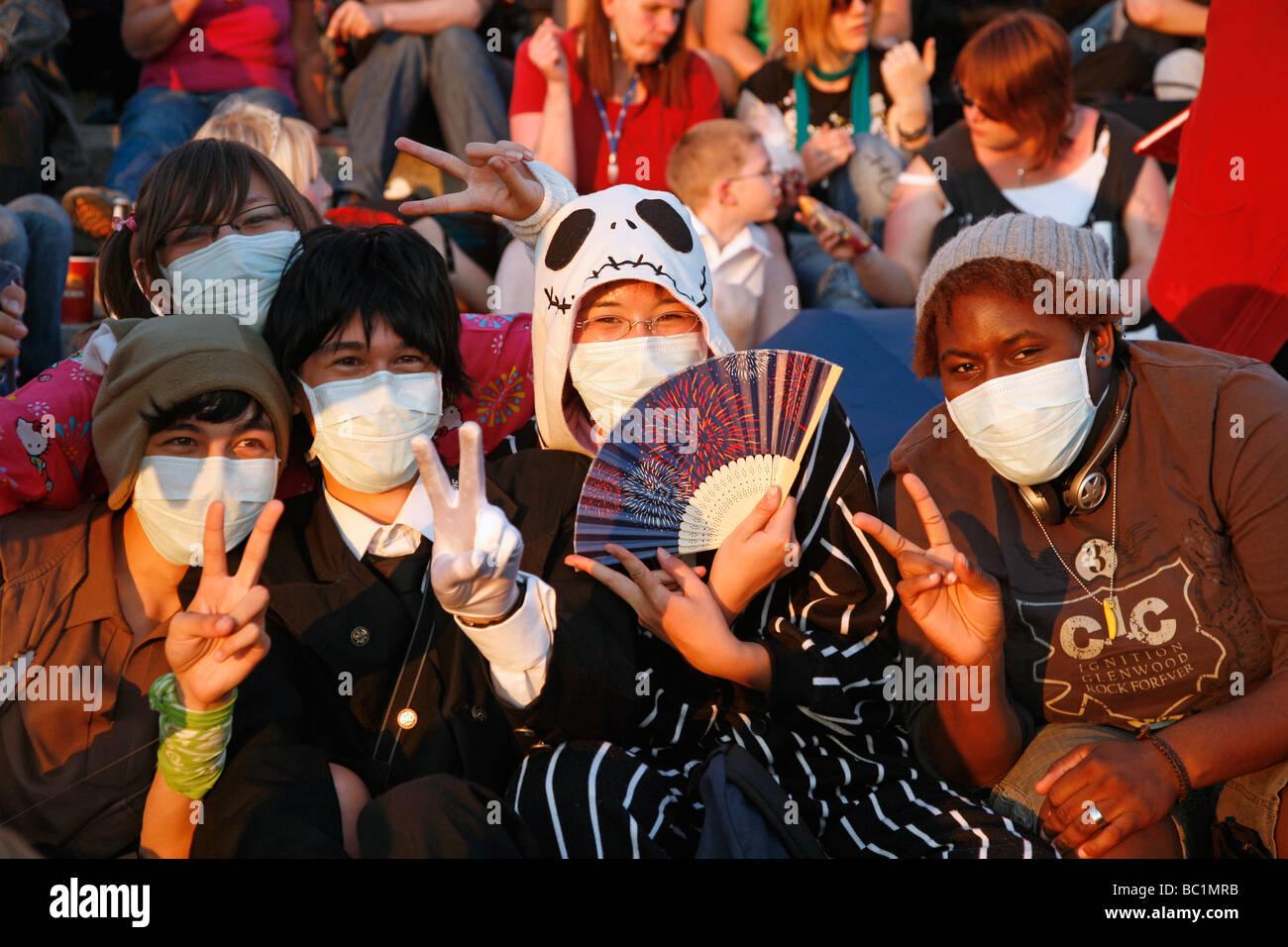 Gruppo di 5 giovani persone che indossano maschere per viso e mostrando il segno di vittoria sul giapponese giorno Immagini Stock