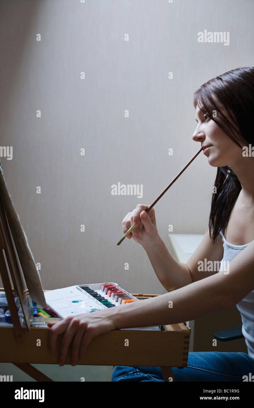 Donna seduta davanti al cavalletto e tenendo il pennello Immagini Stock