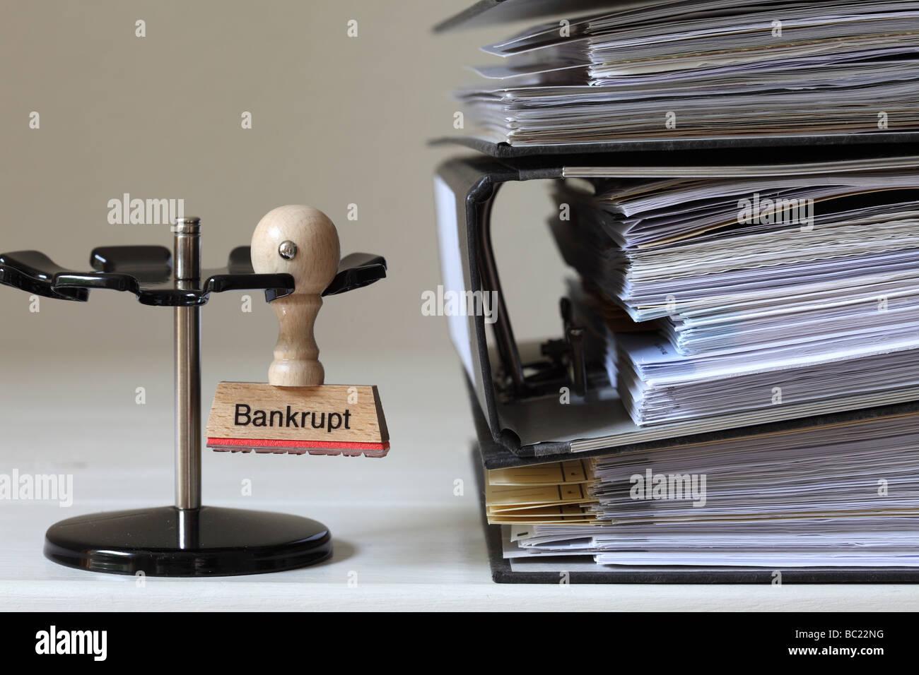 Timbro con iscrizione in bancarotta accanto a una pila di file Immagini Stock