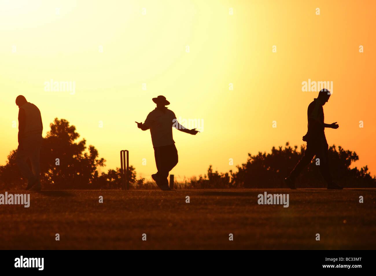 Arbitro e due giocatori di cricket in una sera d'estate. Immagini Stock