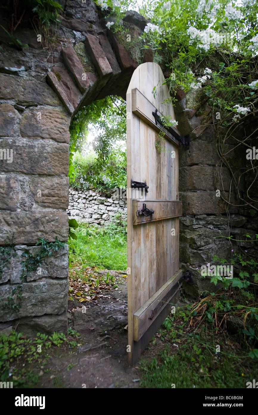 Rovere tradizionale mezza porta aperta nella parete del giardino con pietra circonda e arch,sovrastata con piante Immagini Stock