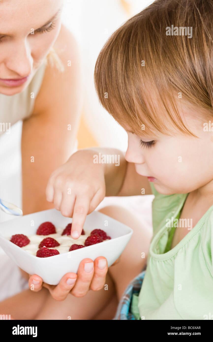 Piccola ragazza di mangiare la prima colazione Immagini Stock