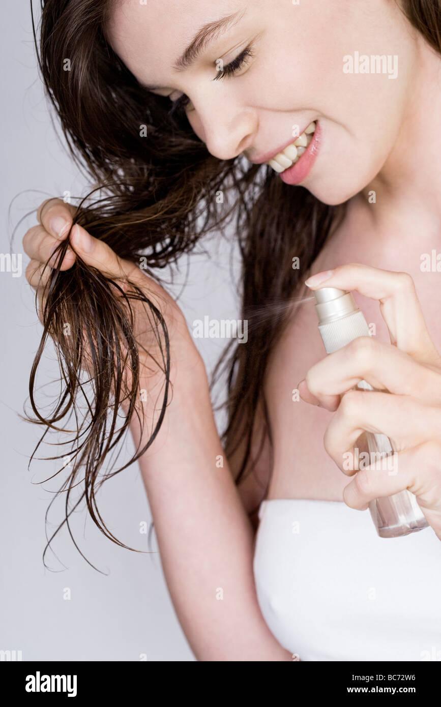 Donna applicazione spray per capelli condizionatore- Immagini Stock