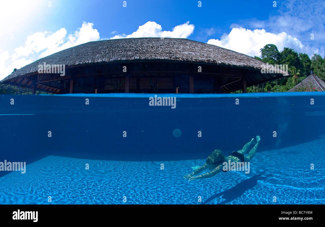 Vista subacquea di una donna che ha appena immerso in una piscina Infinity Immagini Stock