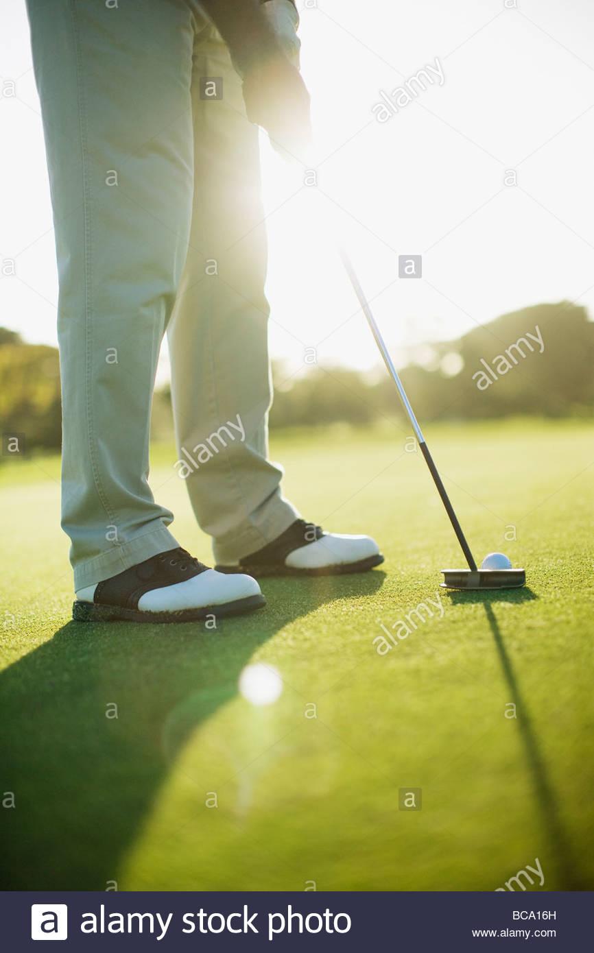 Uomo che utilizza putter per giocare a golf Immagini Stock