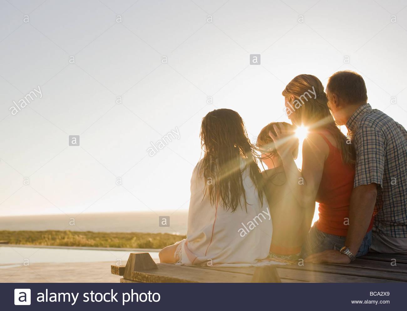 Famiglia seduta sul ponte nel sole del pomeriggio Immagini Stock