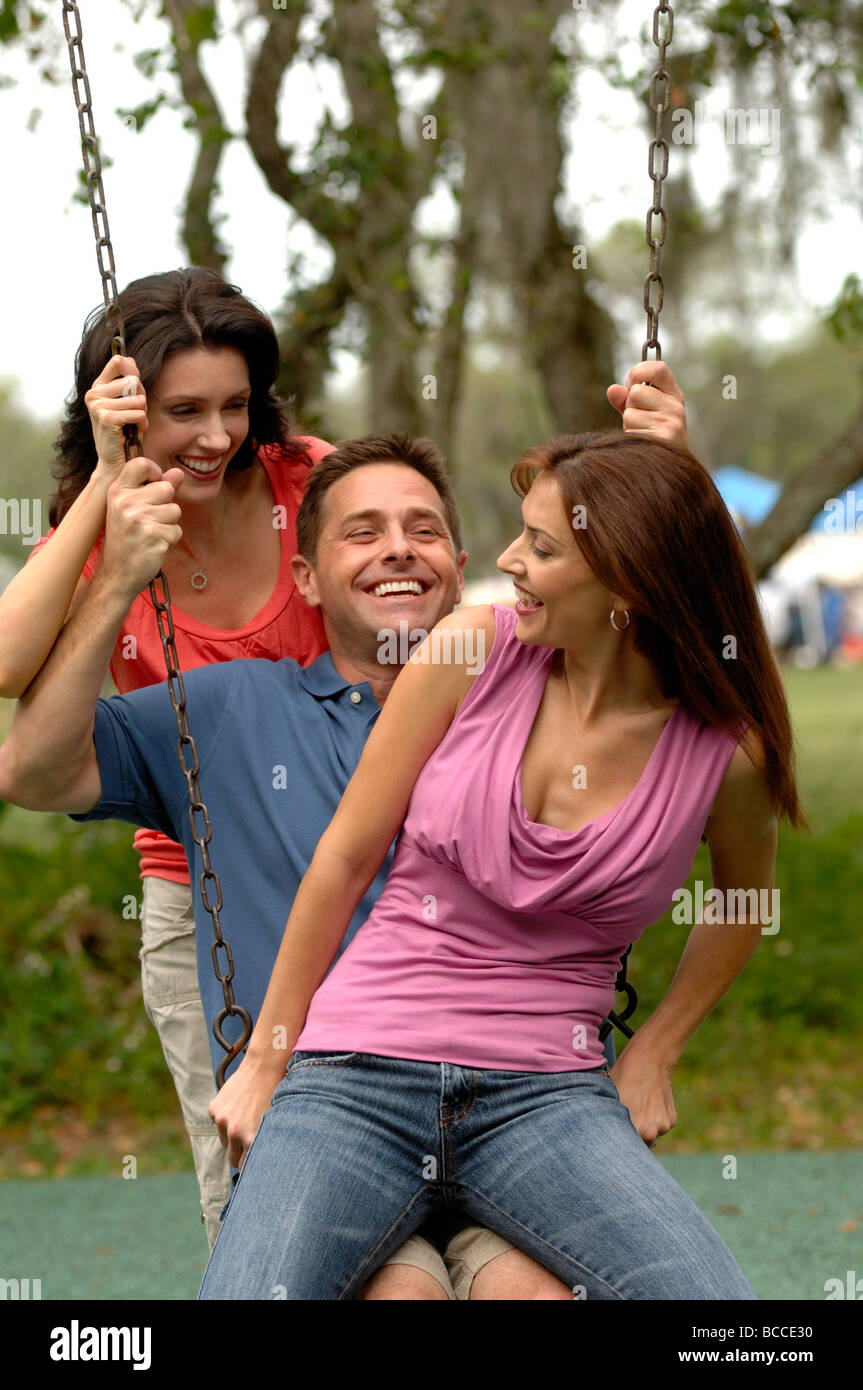 Tre persone giovani adulti (25-35) ingannare intorno sul parco giochi altalena in Florida il parco di quartiere Foto Stock