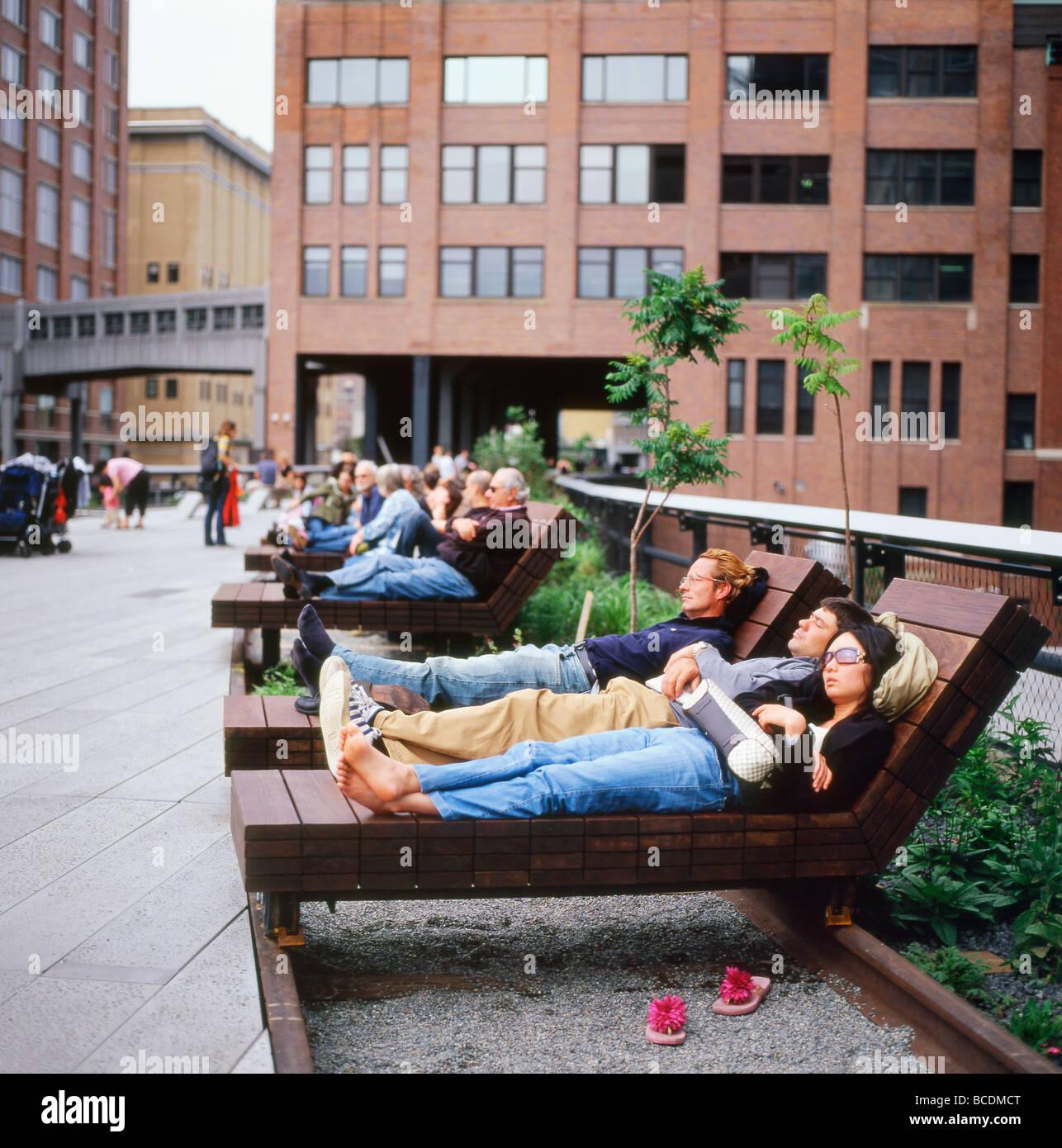 Le persone al di fuori di rilassante onan legno Ipe chaise lounge poltrona reclinabile di mobili di alta linea park Immagini Stock