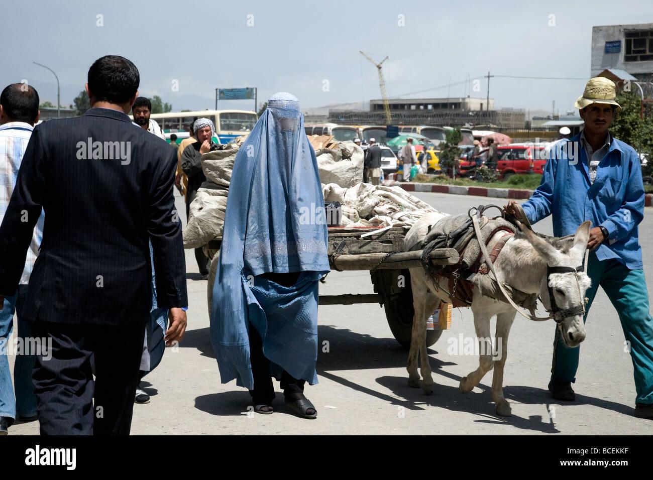 Un mix di vestiti e culture di business suit blu burqa a donkey cart in una trafficata strada di Kabul, Afghanistan Immagini Stock