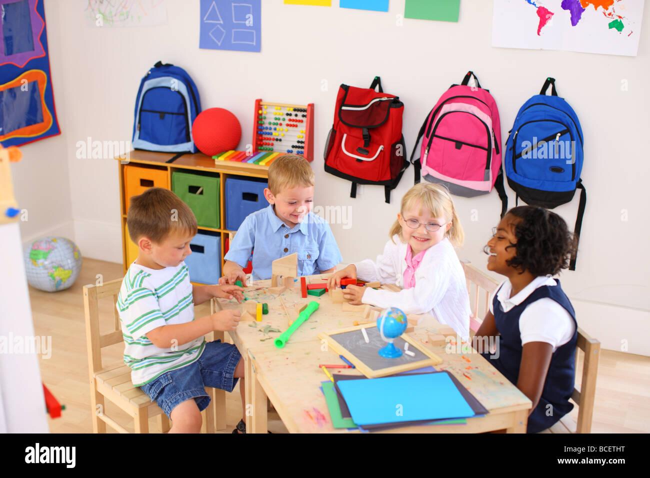Quattro bambini che giocano nella classe di età prescolare Immagini Stock