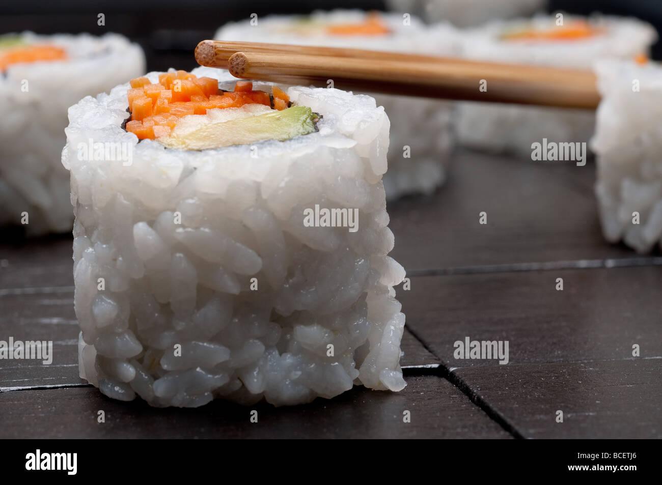 Orizzontale poco profonda focus macro di sushi con copsticks su un nero lo sfondo di legno Immagini Stock