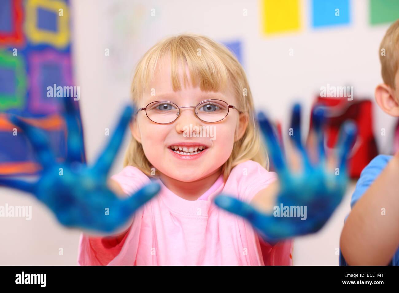 Ragazza in età prescolare con mani coperte di vernice Immagini Stock