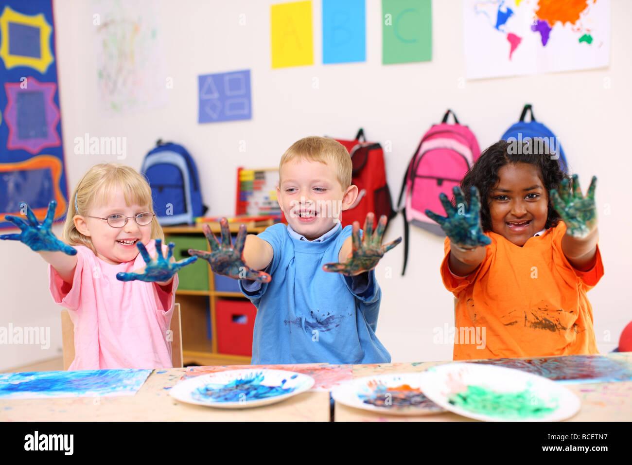 Tre bambini in età prescolare con mani coperte di vernice Immagini Stock