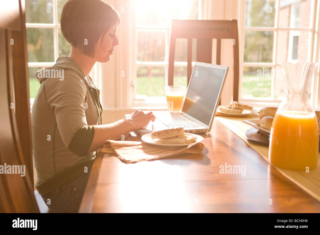Giovane donna con il suo computer portatile per la prima colazione Immagini Stock