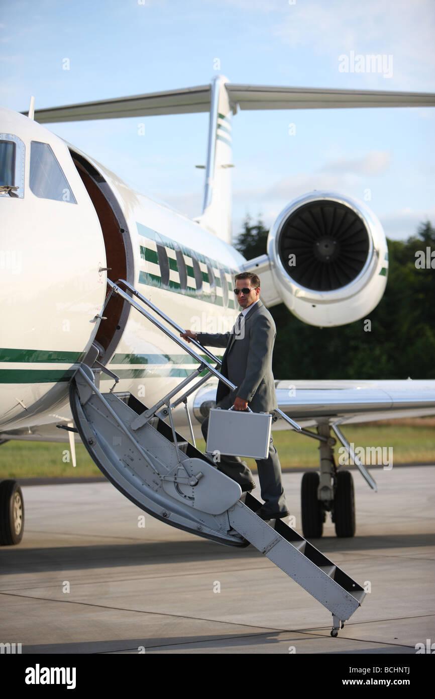 Imprenditore in piedi sulle scale per jet privato Immagini Stock
