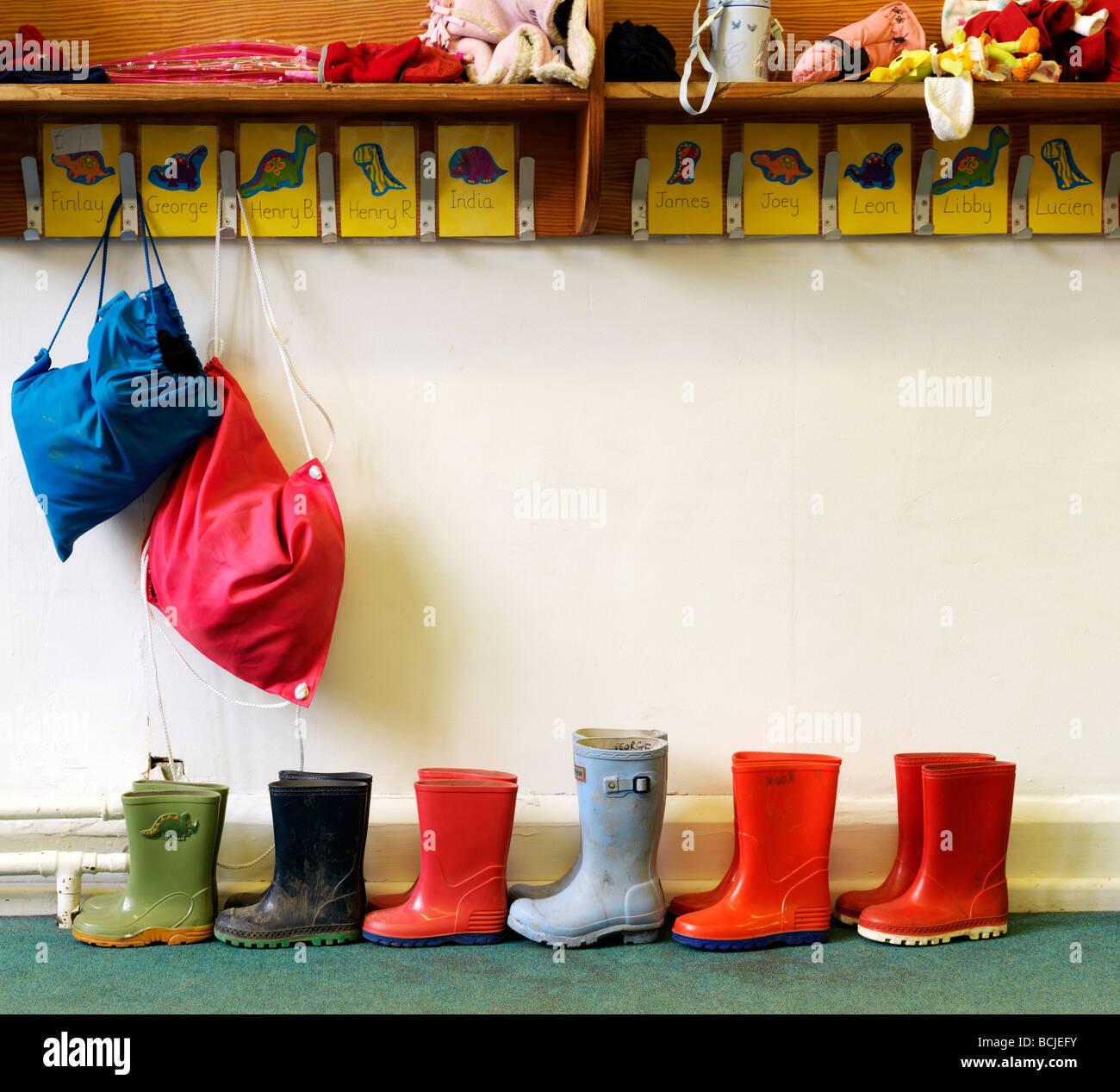 Bambini stivali da pioggia nella scuola vicino a pioli Immagini Stock