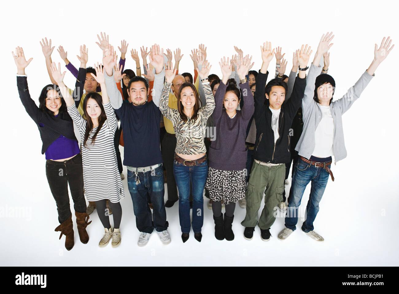 Persone con le braccia alzate Foto Stock