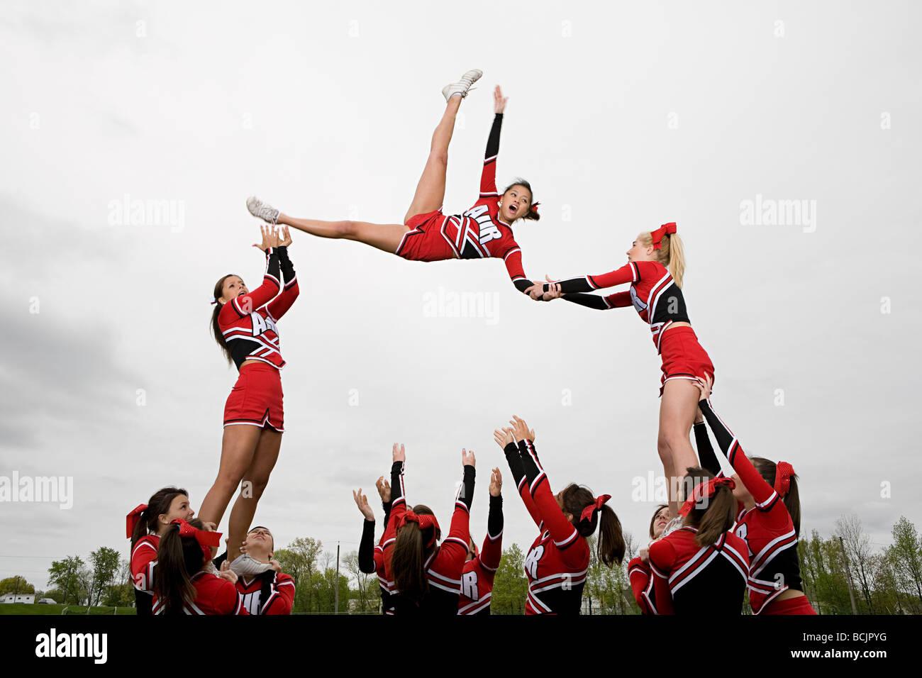 Cheerleaders di eseguire la routine Immagini Stock