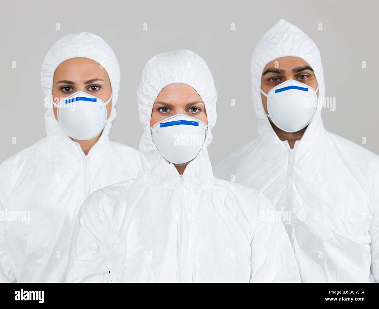 Tre scienziati indossando tute di protezione Immagini Stock