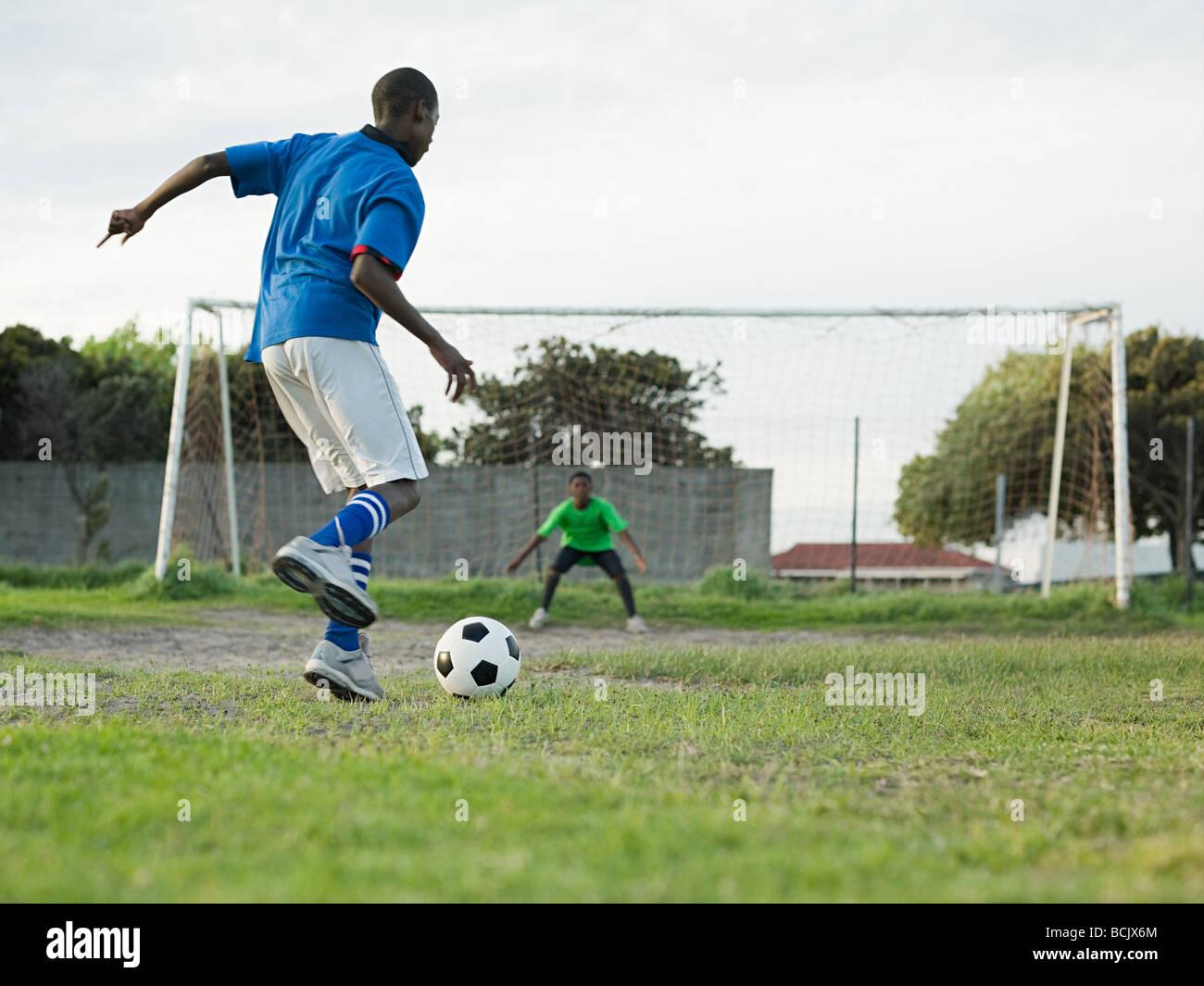 Ragazzi adolescenti a giocare il gioco del calcio Immagini Stock