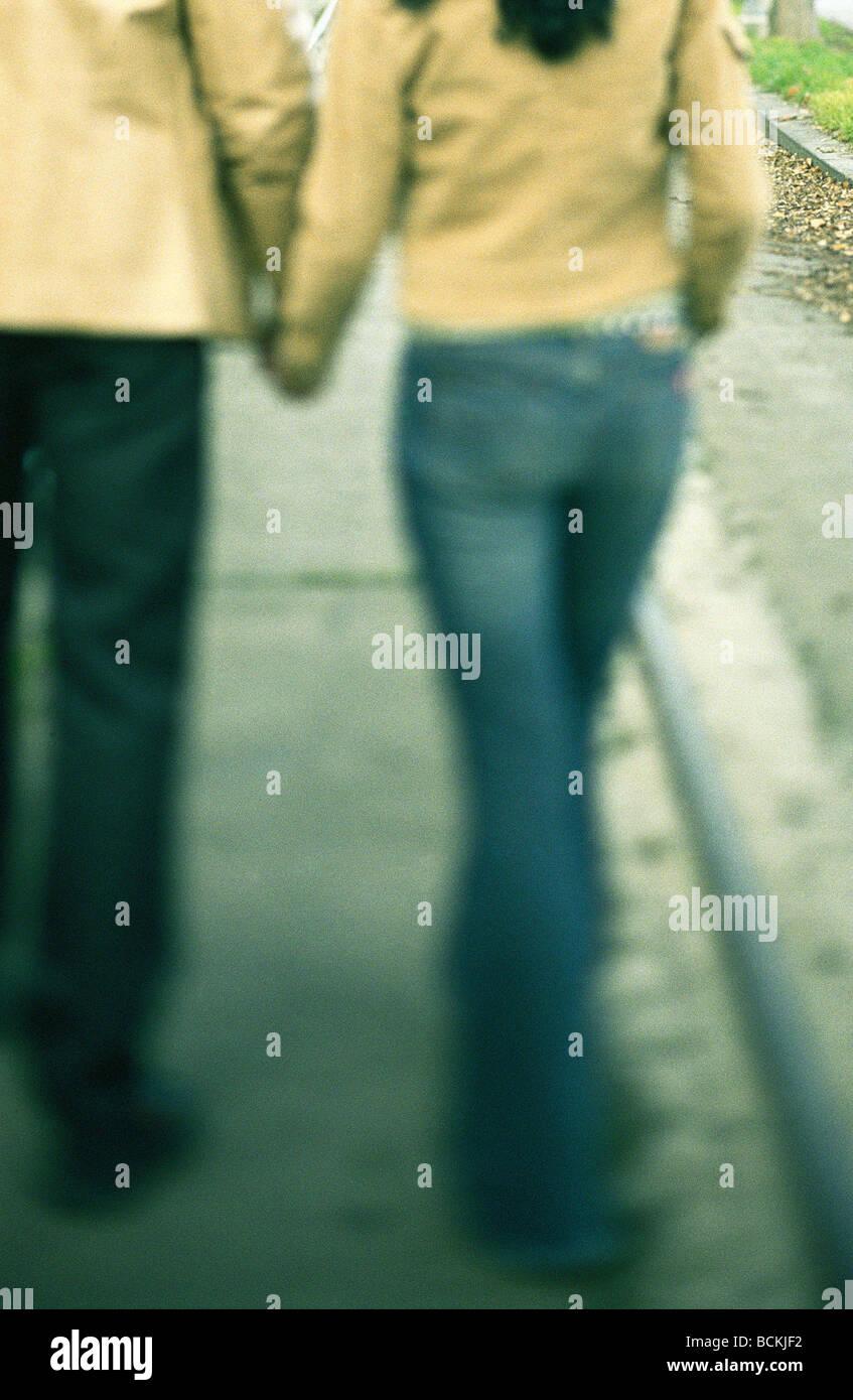 Giovane camminare tenendo le mani sul marciapiede, parte inferiore Immagini Stock