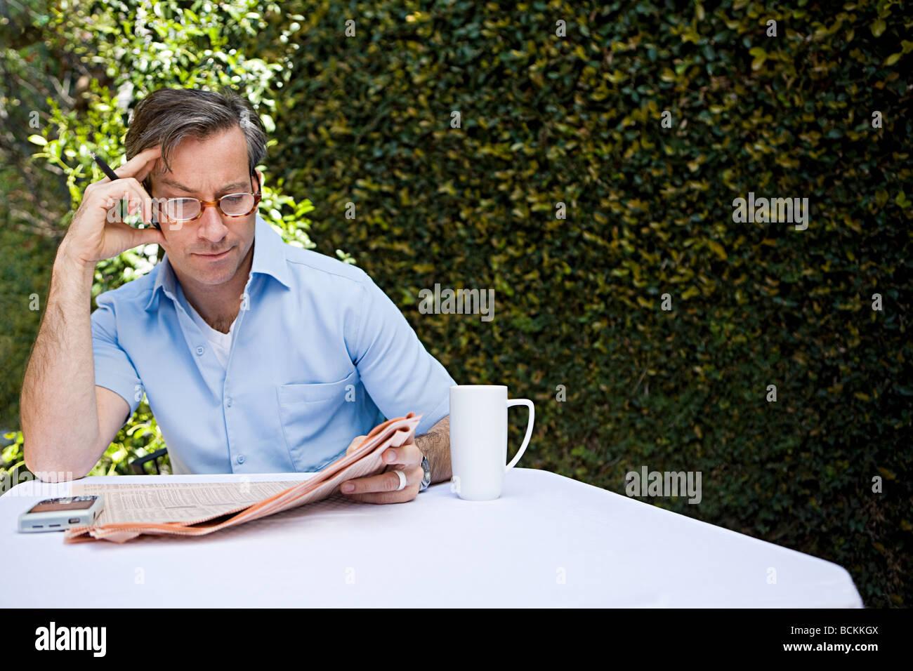 L'uomo all'aperto con quotidiano Immagini Stock