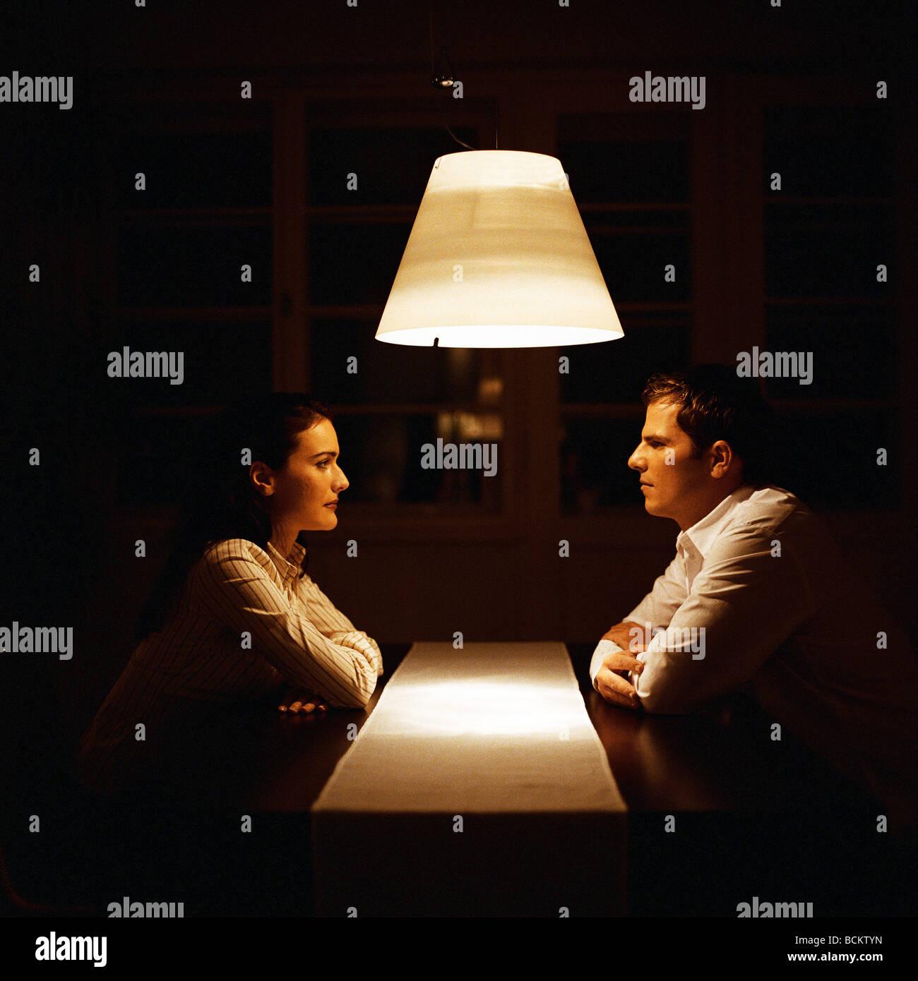 L uomo e la donna faccia a faccia a tavola Foto Stock