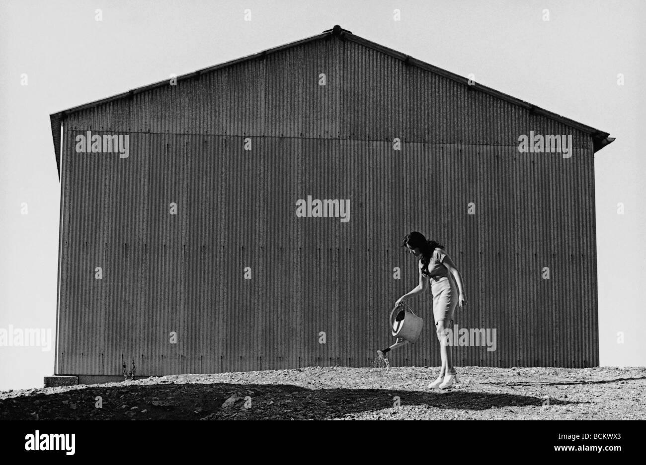 Donna di massa di irrigazione con annaffiatoio dietro il magazzino, b&W Immagini Stock