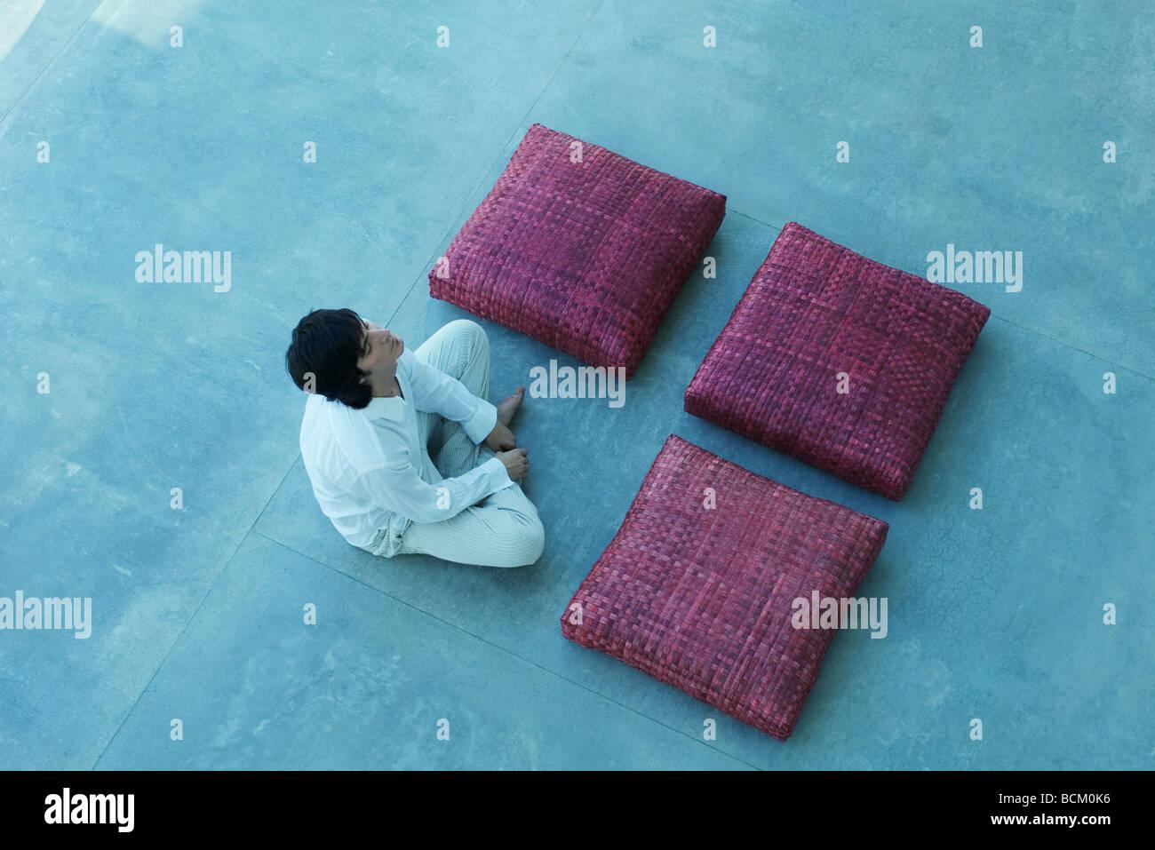 Tre cuscini quadrati e uomo disposti in forma quadrata, uomo gambe incrociate, chiudendo gli occhi, ad alto angolo Immagini Stock