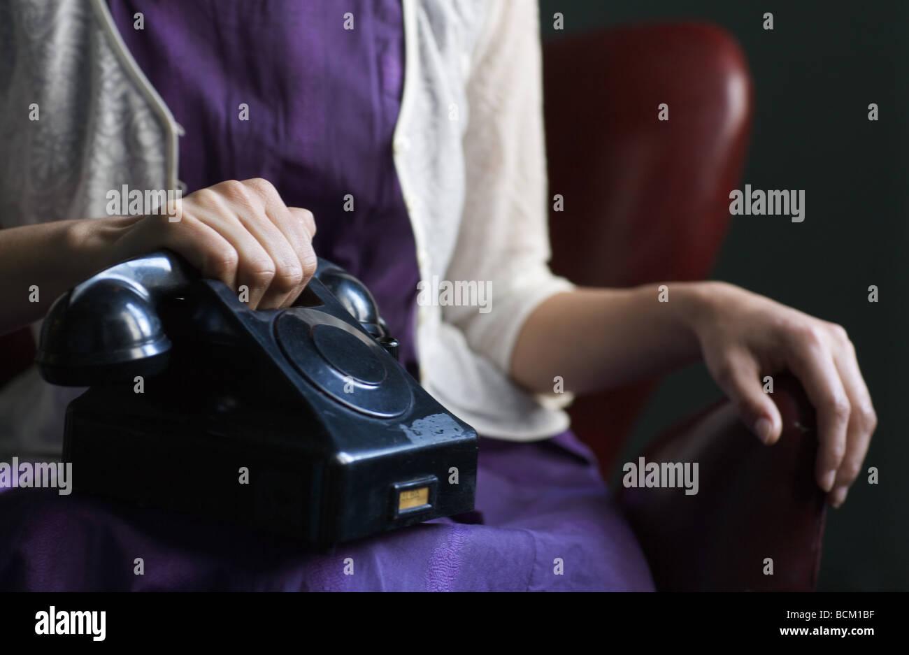 Donna abito in udienza con il telefono sul giro, mano sul ricevitore, vista ritagliata della sezione centrale Immagini Stock