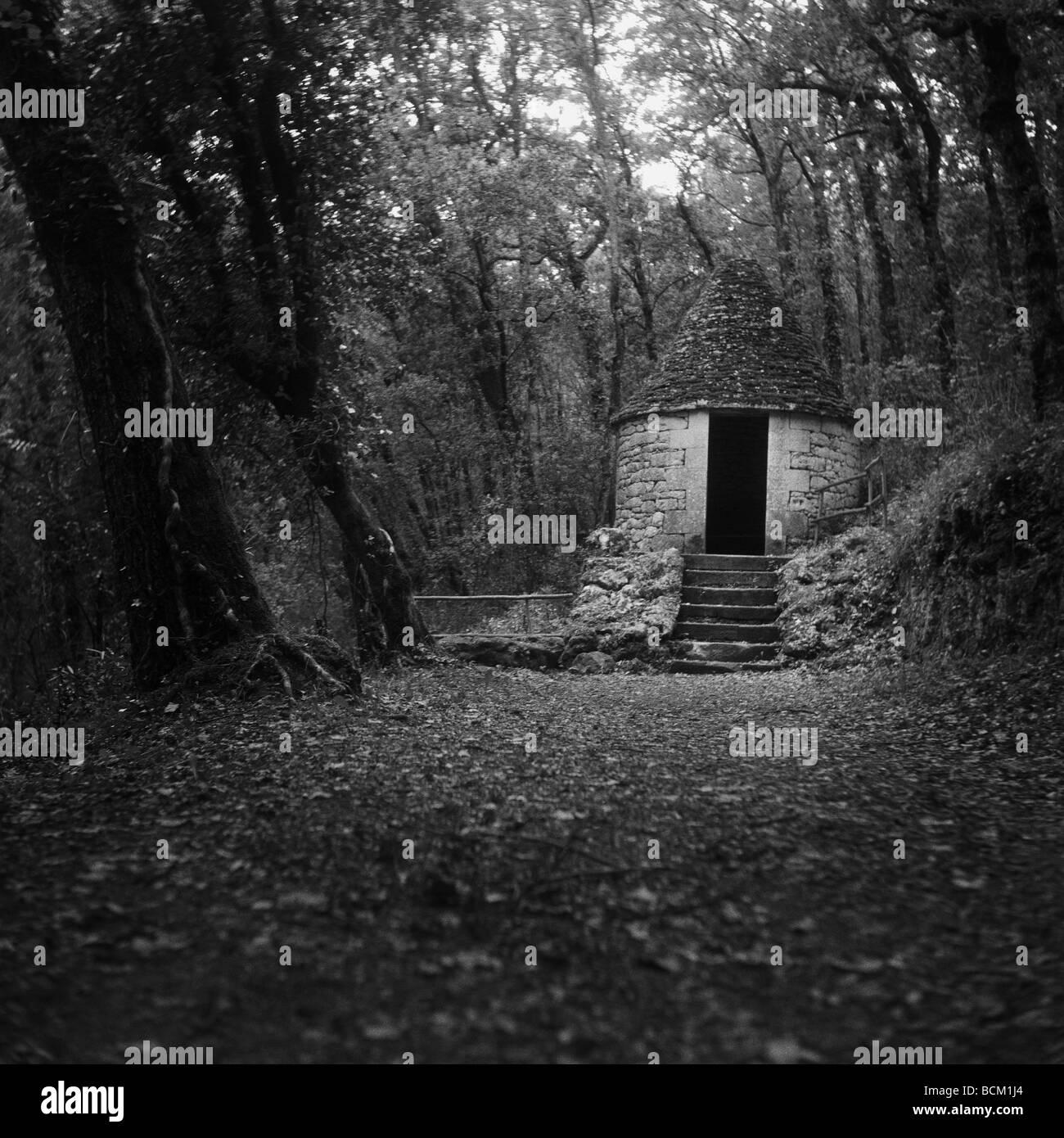 Piccolo edificio di pietra nei boschi, in bianco e nero Immagini Stock