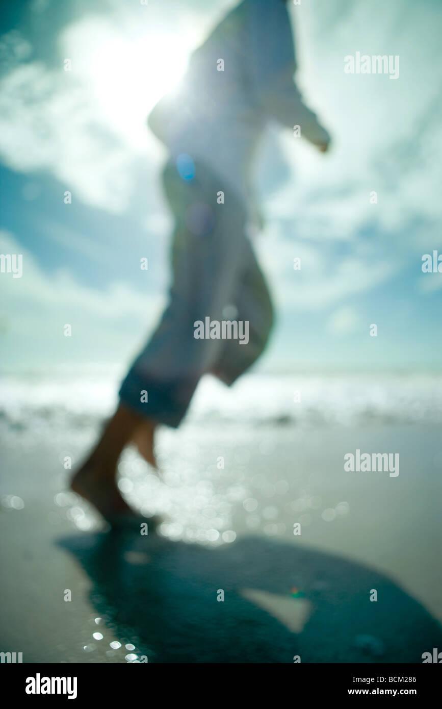 Uomo che corre in spiaggia, vista ritagliata, sfocato Immagini Stock