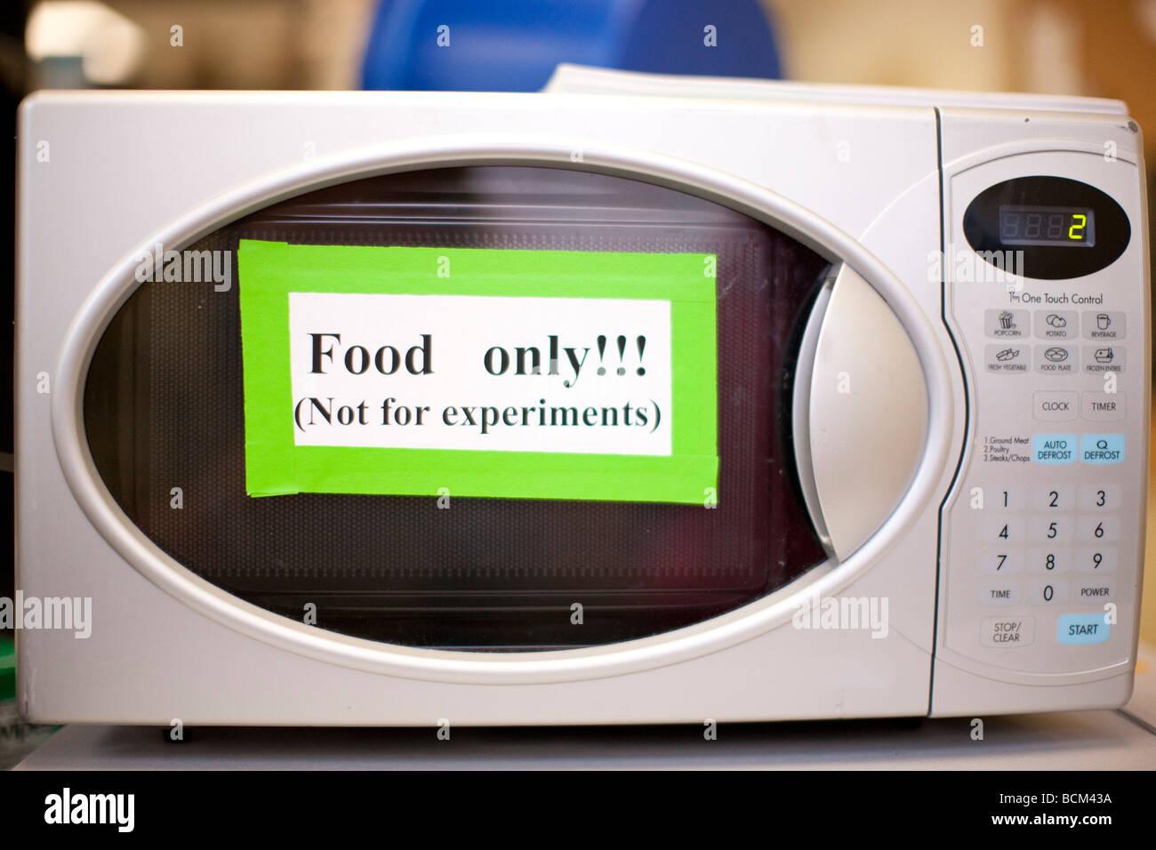 Forno a microonde in laboratorio con segno dicendo il cibo non solo per gli esperimenti Immagini Stock