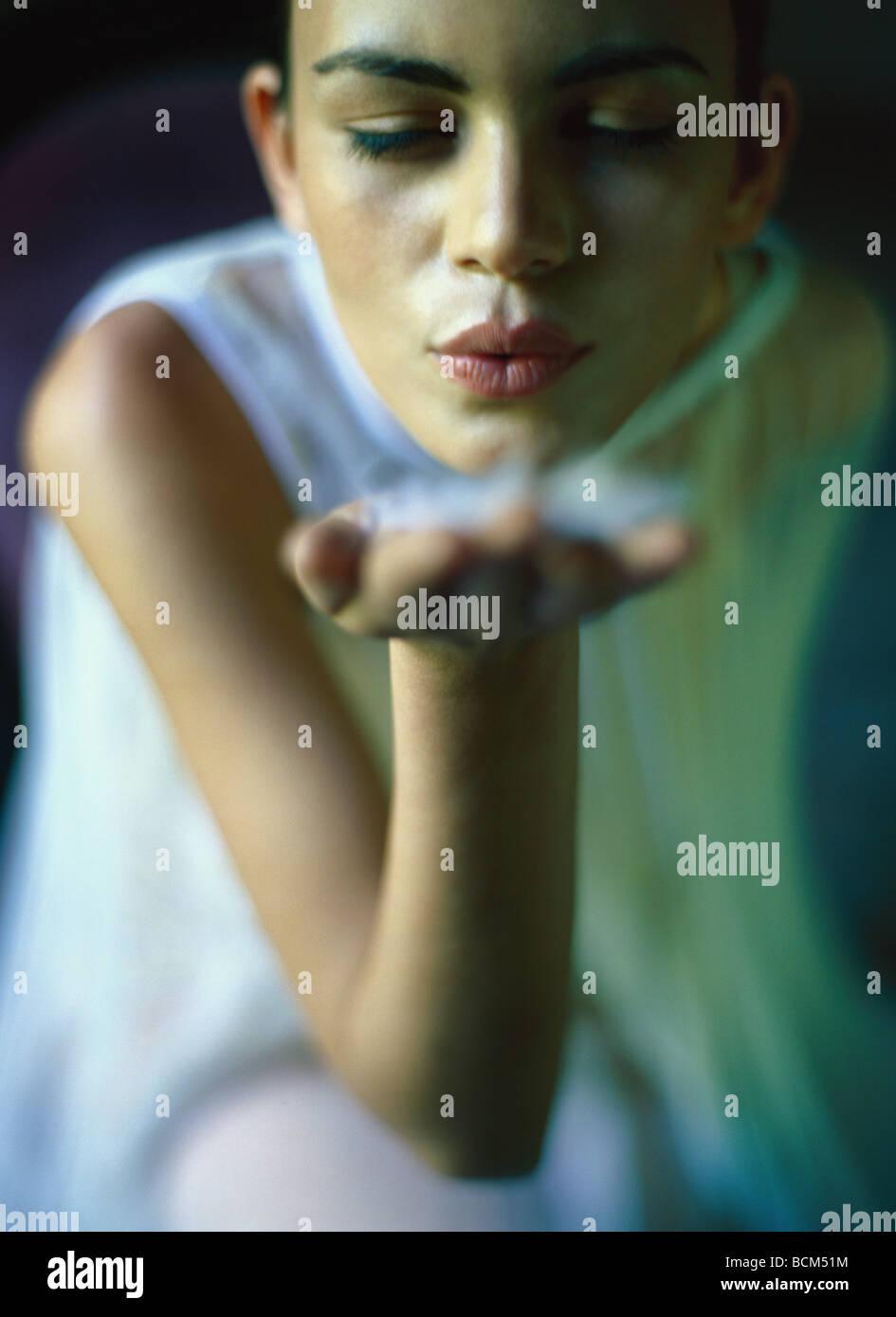 Donna che mantiene fino a mano di soffiaggio, giù, close-up Immagini Stock