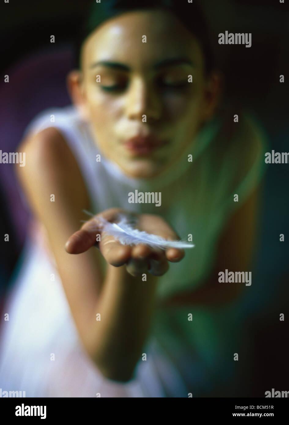 Donna di piume di soffiaggio in mano a occhi chiusi Immagini Stock