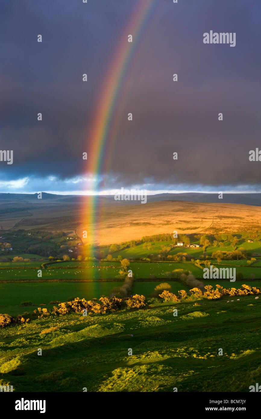 Rainbow al di sopra di terreni agricoli di rotolamento sui bordi del Parco Nazionale di Dartmoor Devon England Primavera Foto Stock