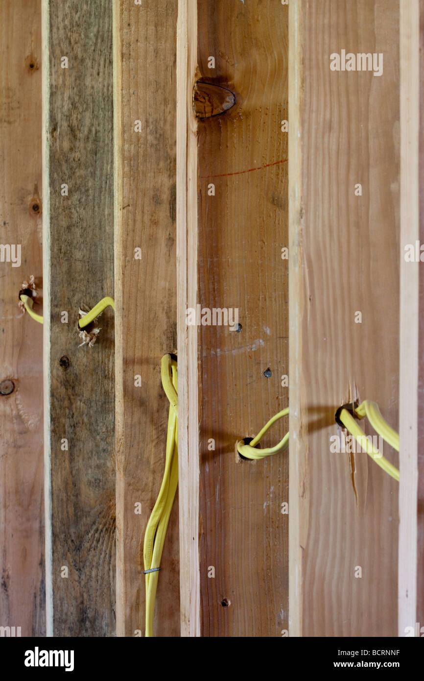 I fili elettrici in esecuzione attraverso la parete di legno prigionieri all'edilizia residenziale sito Foto Stock