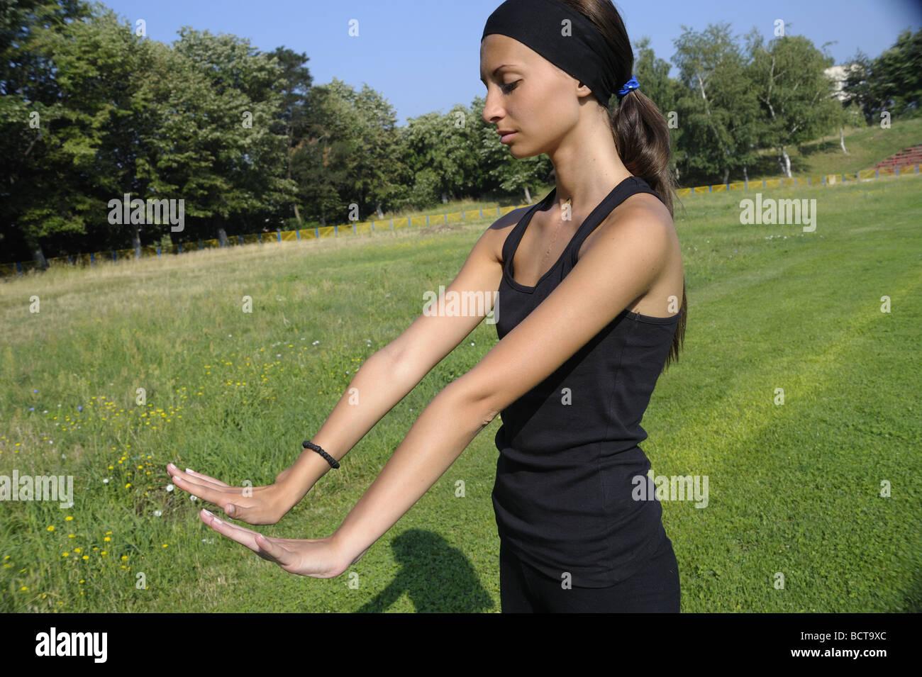 Ragazza facendo esercizi di stretching per le mani e i polsi - ai polsi di piegatura verso l'alto Foto Stock
