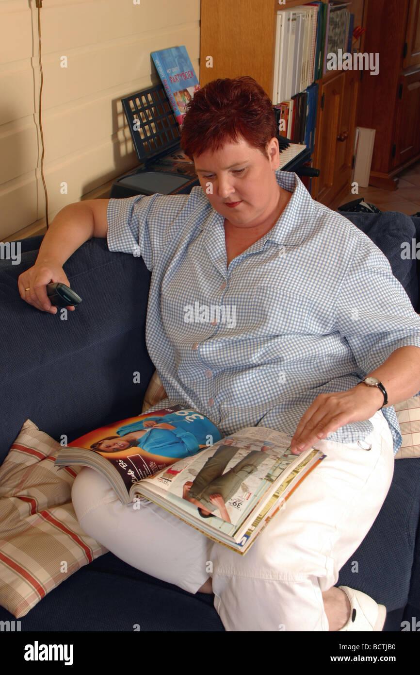 Donna adulta a sedersi su un divano, shopping da home catalogo Immagini Stock