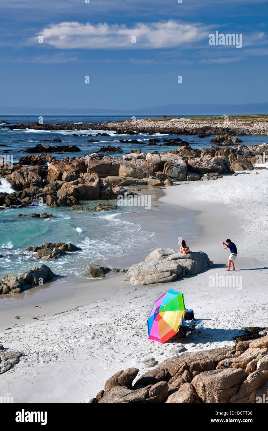 Ombrellone e spiaggia con uomo di scattare una foto di famiglia 17 Mile Drive Pebble Beach in California Immagini Stock