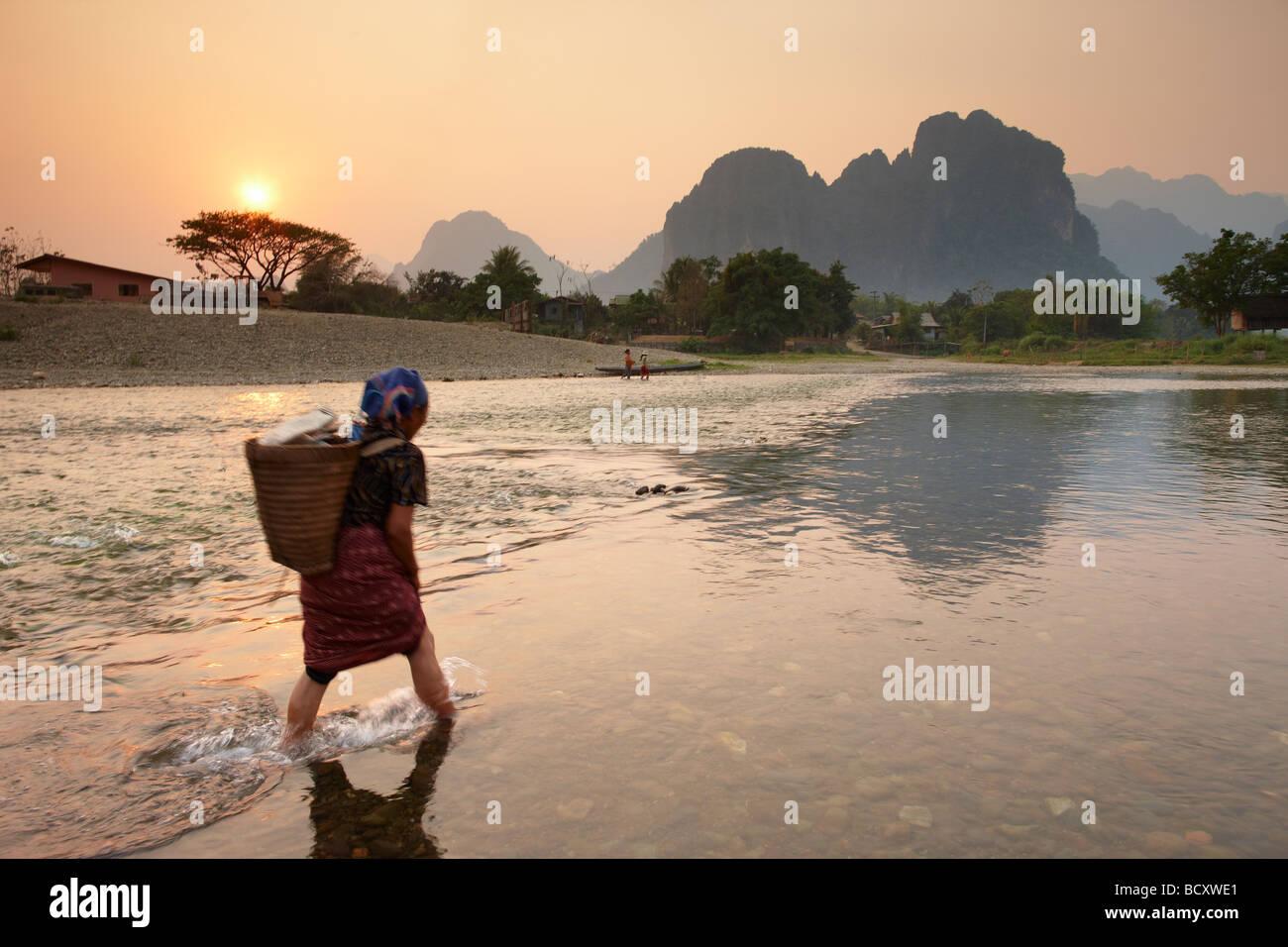 Una donna guadato il Nam Song River a Vang Vieng, Laos Immagini Stock