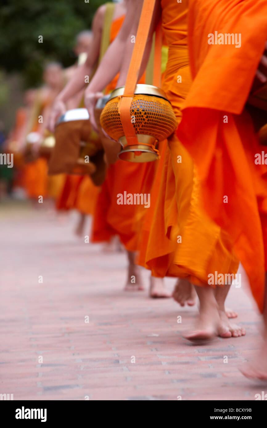 La processione di monaci all'alba attraverso il paese per raccogliere doni alimentari, Luang Prabang, Laos Immagini Stock