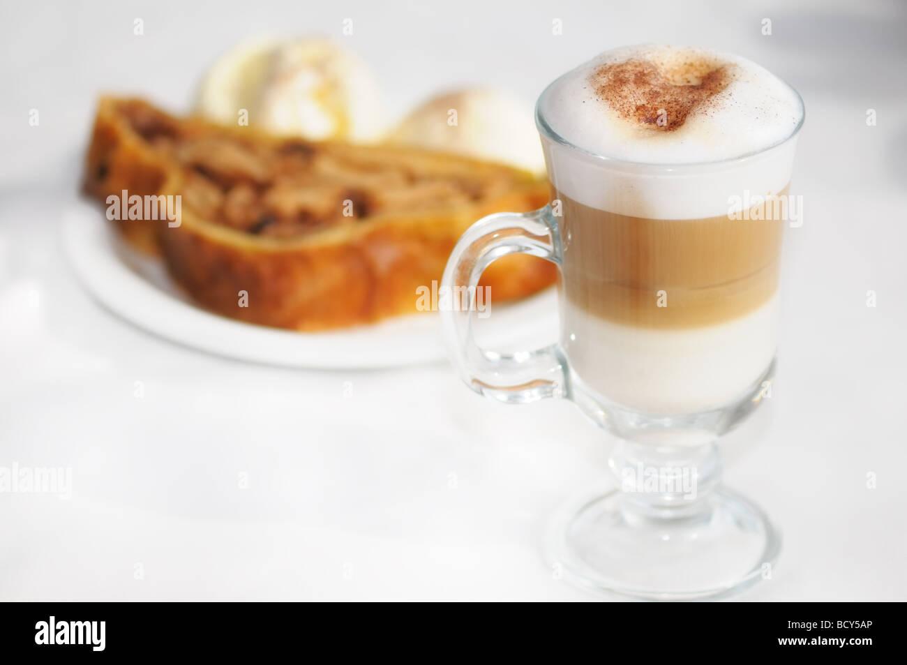 Un cappuccino caldo coppie piacevolmente con il caldo lo strudel di mele e gelato. Immagini Stock