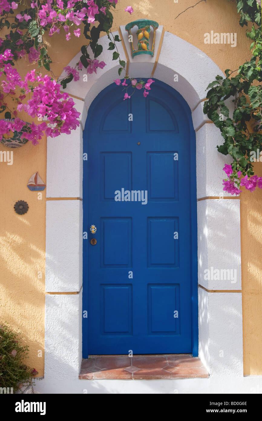 Bougainvillaea a parete gialla e blu porta in Greco Assos Immagini Stock