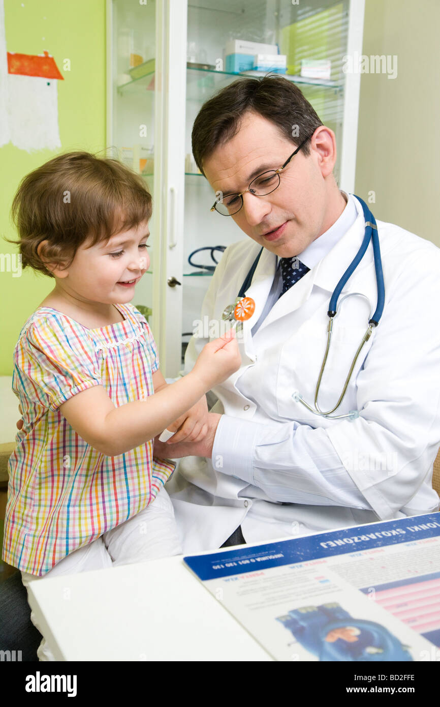 Medico dando per lecca-lecca pop per il toddler girl Immagini Stock