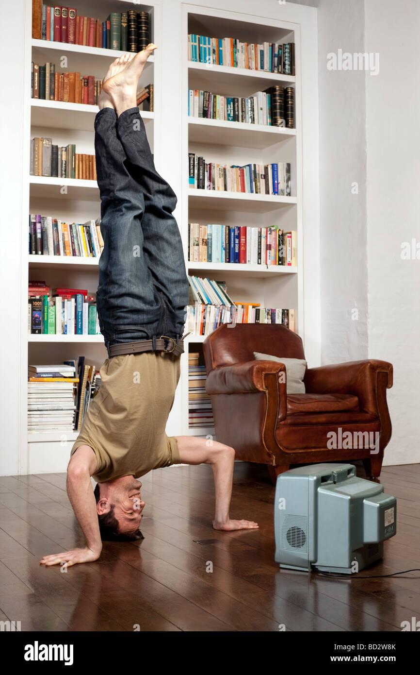 Uomo in piedi sulla testa con tv Immagini Stock