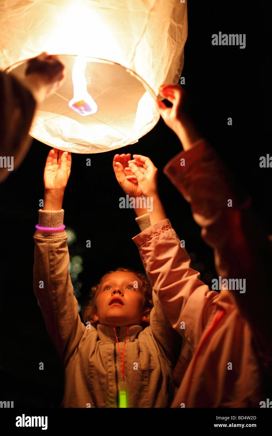Kids lanciare una lanterna sky; lanterna tailandese; LANTERNA OSCILLANTE; modello di rilascio disponibili per la Immagini Stock