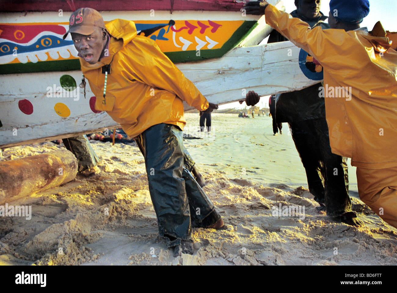 Gli uomini aiutare a spingere una barca sulla battigia in Africa occidentale. (Foto di Ami vitale) Immagini Stock