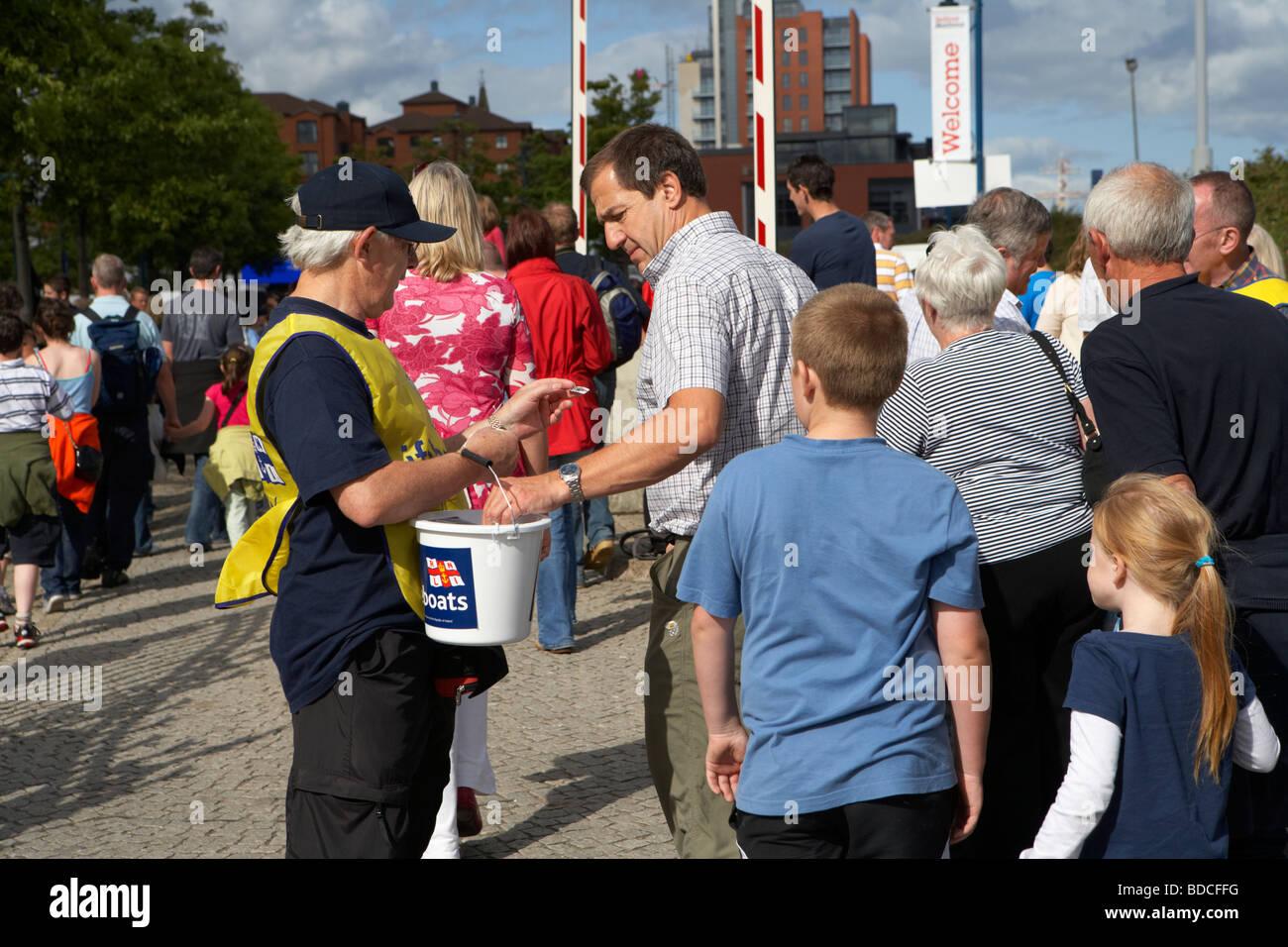 Volunteer facendo una carità la benna di raccolta per il RNLI in un affollato evento outdoor a Belfast Irlanda Immagini Stock