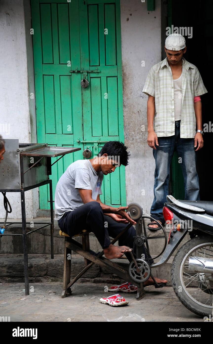 L'uomo affilare i coltelli utilizzando una bicicletta atto capovolta hanuman dhoka Durbar Square Kathmandu in Immagini Stock